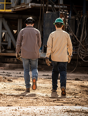 Two men walking in a work site